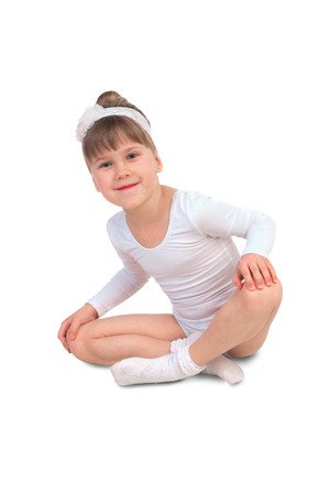 leotard: Little girl in a ballet leotard sitting in lotus position on a white background Stock Photo