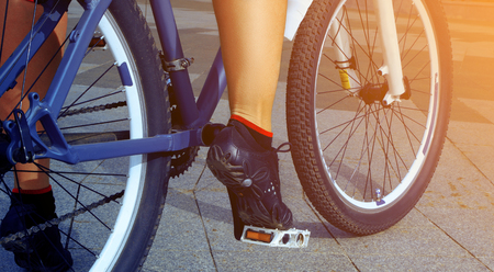 bicycle pedal: girl legs in sneakers on the bicycle pedal close up outdoors Stock Photo