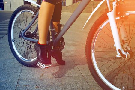 piernas mujer: mujer hermosas piernas en zapatillas de deporte en el pedal de la bicicleta se cierran para arriba