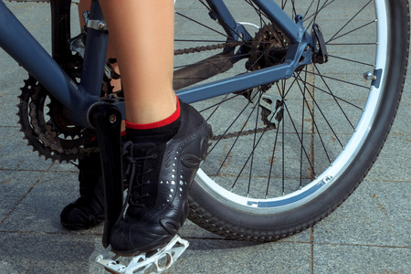 pedal: horizontal picture of female legs in sneakers on the bicycle pedal