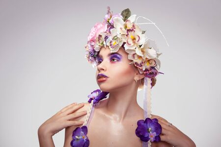 female sexuality: Gorgeous young girl with wreath on head and makeup in purple tones looking away in studio on grey background Stock Photo