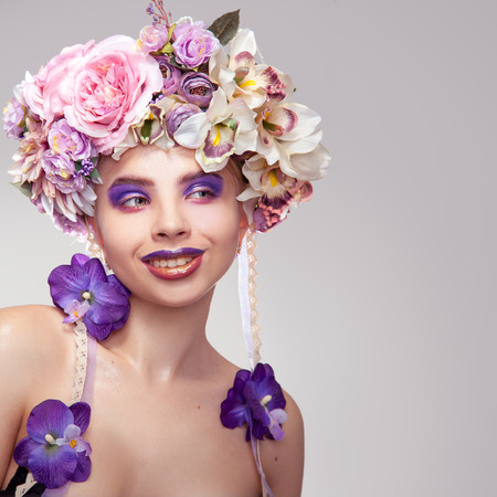 female sexuality: Square photo of Happy young girl with wreath on head and makeup in purple tones looking away in studio on grey background