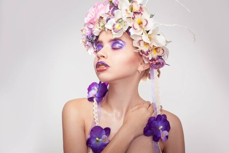 female sexuality: fresh portrait of young woman with wreath on head and makeup in purple tones with closed eyes in studio on grey background