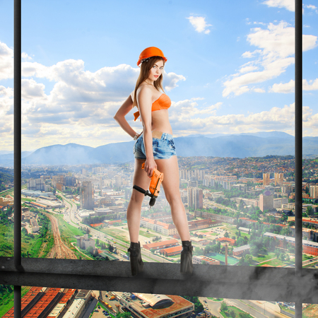 Sensual woman builder in helmet and drill in hands standing on a crossbar high above the city  and looking at the camera Stock Photo