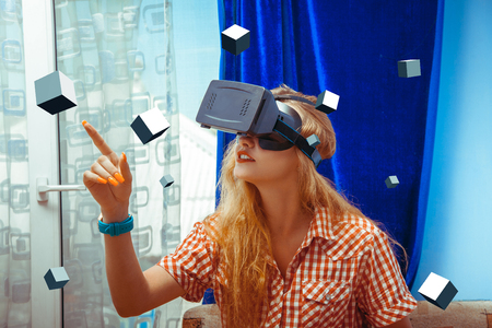 woman in virtual reality glasses touch a 3d cube. VR helmet. third dimension. Virtual reality glasses. Stock Photo