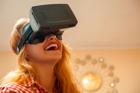 horizontal portrait of young beautiful girl in virtual reality helmet smiling. VR helmet. third dimension. Virtual reality glasses. Stock Photo