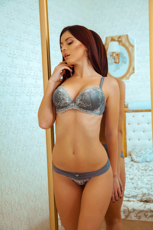 whore: woman in beautiful lingerie posing near a mirror with closed eyes at home Stock Photo