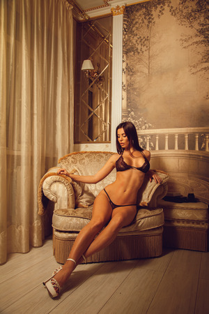 slim sexual young woman in beautiful lingerie sits on a soft chair with closed eyes and open mouth at home