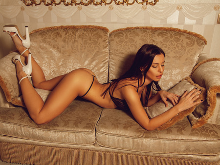 whore: Seductive young woman in beautiful lingerie lying on the sofa with closed eyes at home Stock Photo