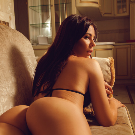 square portrait of young gorgeous woman in lingerie with beautiful round ass lying on sofa at home