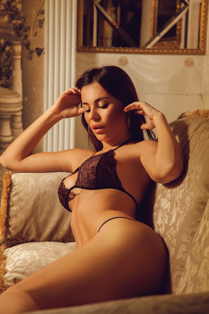seductress: vertical portrait of sexual young brunette woman in beautiful lingerie on the sofa Stock Photo