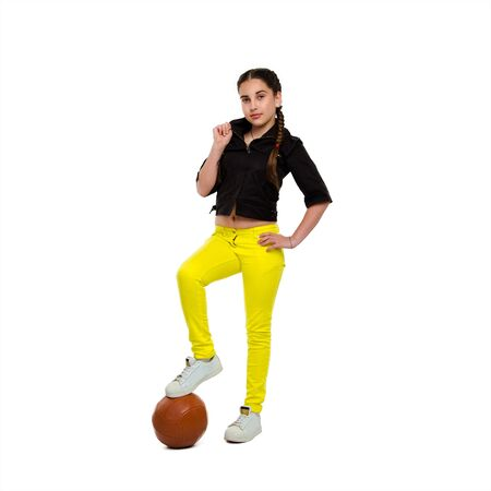 full length portrait of young girl with orange ball in studio looking at the camera isolated on white background Stock Photo