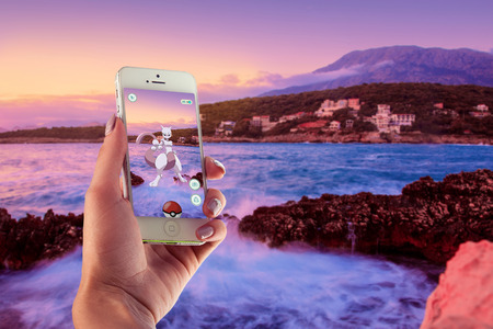 ios: Bar, Montenegro - 9 July 2014: White Apple iPhone 5s held in one hand showing its screen with Pokemon Go application Editorial