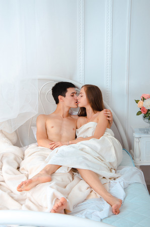 young lovers without clothes lying in white bed and kissing Stock Photo