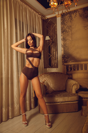 seductress: portrait of sexual young woman in beautiful lingerie on high heels at home Stock Photo