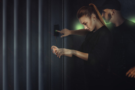 hack: horizontal Photo robbery guy with the girl in black suits hack an electronic lock on the safe Stock Photo