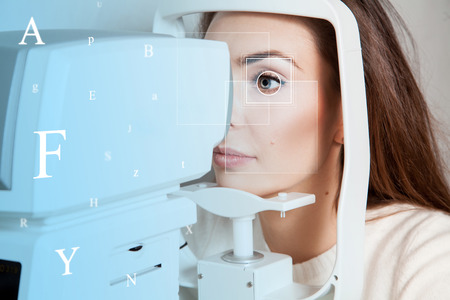 future medicine: Charming young brunette in the future clinic checks her vision with virtual letters in the air. Ophthalmologist. Virtual sensor for checking vision. Future medicine concept. Stock Photo