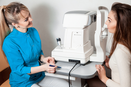 fundus: woman ophthalmologist diagnoses her young patient after survey and smiling to her. Ophthalmologist. medical, health, ophthalmology concept. Stock Photo