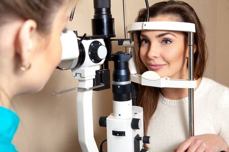 Beautiful girl patient checks her vision at the ophthalmologist and smiling to her. Ophthalmologist. medical, health, ophthalmology concept