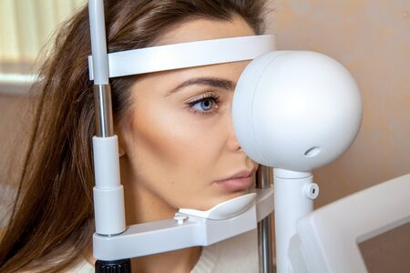 young brunette lady with blue eyes checks her sight at the ophthalmologist. Ophthalmologist. medical, health, ophthalmology concept