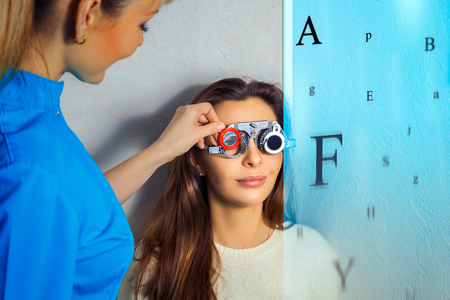 future medicine: Beautiful young brunette girl checks her vision at the ophthalmologist. Future medicine concept art with virtual vision checking and with corrective lenses. Stock Photo