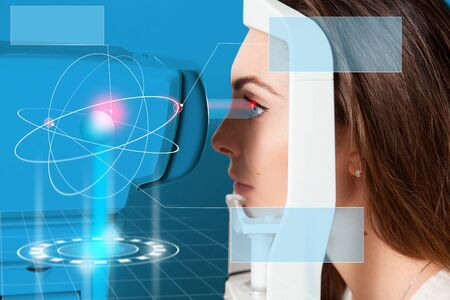 future medicine: beautiful young girl checks eyesight on Autoceratorefractometers. Future medicine concpet art with Virtual Reality in the hologram shows the eye disease