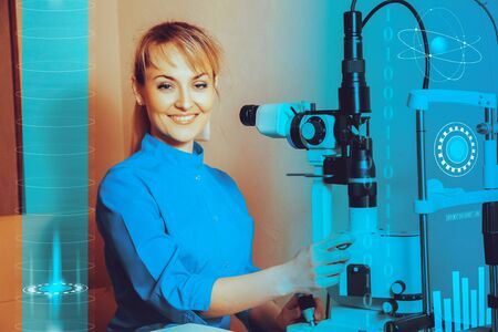 future medicine: Happy young beautiful Doctor at work machine for checking vision smiling on camera. Future medicine concept art with machine for checking sight.