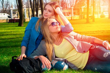 cute girlfriends: Two cute girlfriends sitting on the grass in the park relaxing and having fun