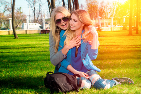 cutie: Two cutie girlfriends sitting on the grass in the park having fun and laughing