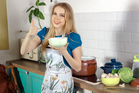 soup bowl: young blonde cook in a chef apron with a bowl of soup in hand showing thumbs up and smiling Stock Photo