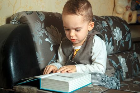 cutie: cutie young boy in elegant suit read a book and sits on a couch Stock Photo