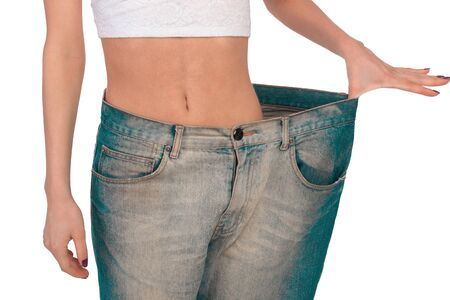 tries: Girl tries on jeans a very large size Stock Photo