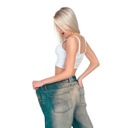 large size: Girl blonde tries on jeans a very large size