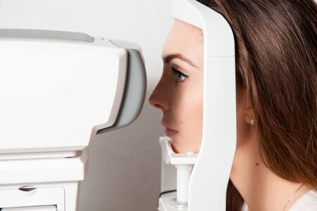 fundus: beautiful young girl checks eyesight on Autoceratorefractometers. Ophthalmologist. medical, health, ophthalmology concept