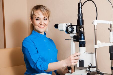 fundus: Happy young beautiful Doctor at work machine for checking vision. Ophthalmologist. medical, health, ophthalmology concept Stock Photo