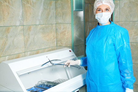 fundus: beautiful young woman doctor gets sterile items required for operation. Ophthalmologist. medical, health, ophthalmology concept