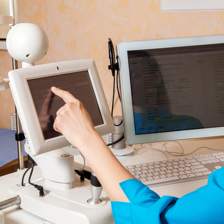 fundus: female doctor hand working on touch screen computer in cabinet. Ophthalmologist. medical, health, ophthalmology concept