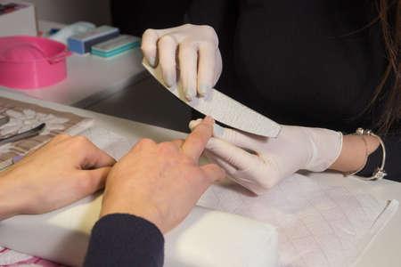 ring finger: Manicurist files ring finger nail