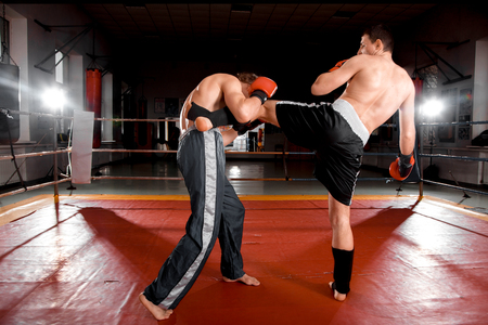 opponent: Man in black shorts is kicking his opponent
