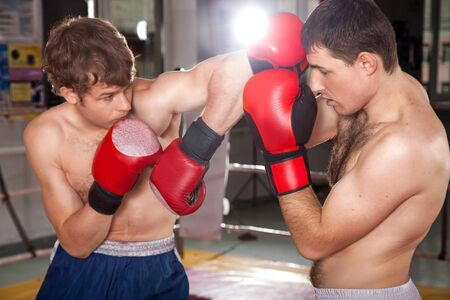 opponent: Man from the left is striking a blow with his elbow to his opponent Stock Photo