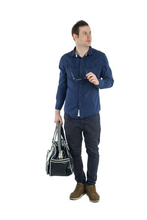 looking aside: Young man in blue shirt and jeans holding black bag and glasses and looking aside