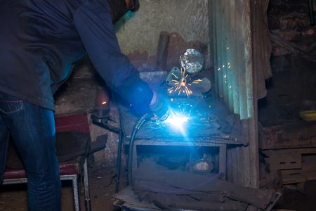 welding machine: Hands in gloves with welding machine