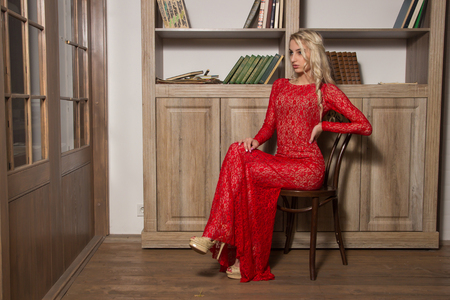 looking aside: Girl in a long red dress in sitting on the chair and looking aside