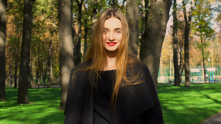 cutie: cutie young woman with red lips in stylish coat looking at the camera and smiling outdoors in the autumn park