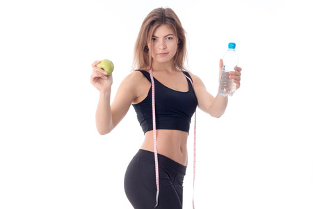 Beautiful slim girl in a black top and tights is turned sideways and stretched out both hands forward shows a fruit and a bottle of water