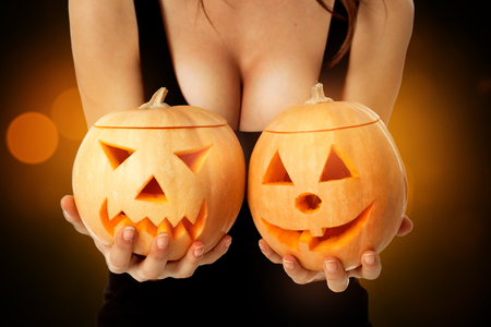 woman with big boobs in halloween style with two pumpkins in hands looking at camera in studio