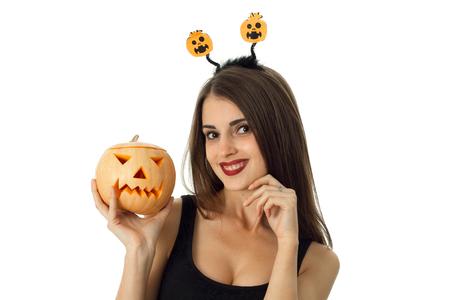 cutie: cutie cheerful girl in halloween style clothes with pumpkin in hands looking at camera in studio isolated on white