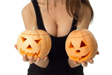 close up of woman with big boobs in halloween style with two pumpkins in hands looking at camera in studio isolated on white Stock Photo