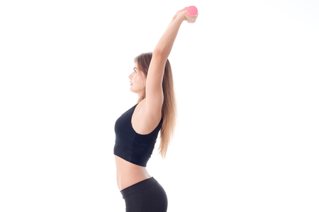 caved: Fitness woman in black sports top side is caved in the back and holding the dumbbells holding up two hands