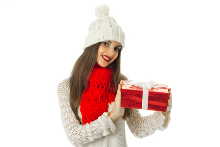 cutie: cutie young brunette woman in warm sweater and red scarf with red gift in hands isolated on white background